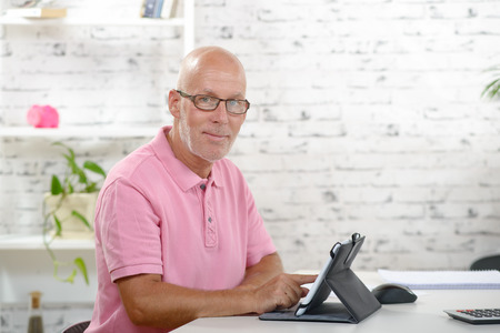 businessman working at his computer: a senior businessman with a pink polo shirt look a digital tablet