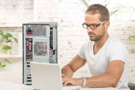 young engineer: young engineer repaired a computer with laptop