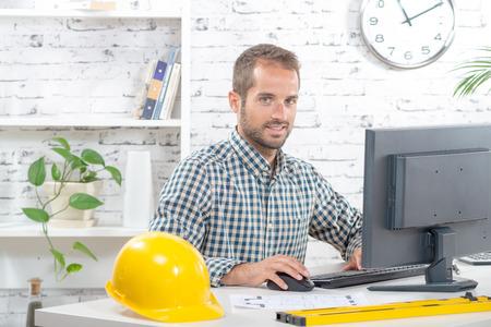 suo: giovane ingegnere che lavora sul suo computer nel suo ufficio