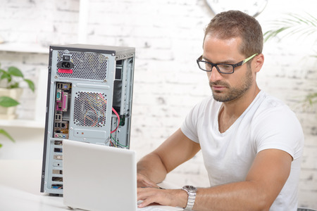 young engineer repaired a computer with laptop