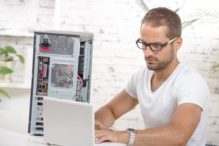 trabajando en computadora: joven ingeniero reparar un ordenador con la computadora port�til