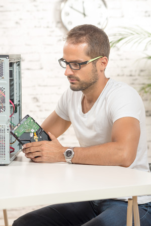 repaired: young engineer repaired a computer with a new hard disk