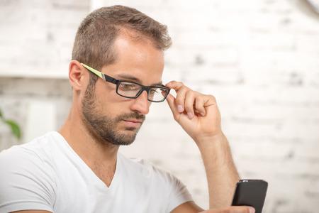 suo: giovane dirigente guardando il suo cellulare nel suo ufficio Archivio Fotografico