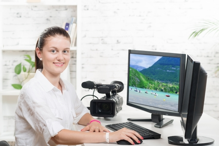 editing: pretty young woman video editor with computer and professionnal video camera