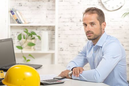 young engineer: young engineer with blue shirt working in his office Stock Photo