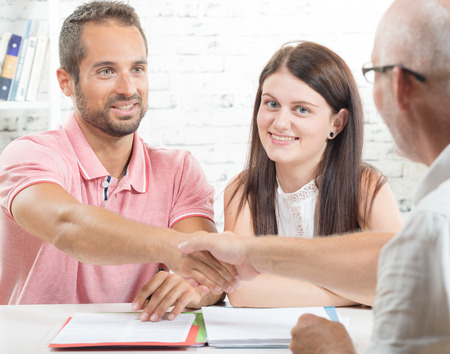 financial agreement: a young couple signs a contract Stock Photo