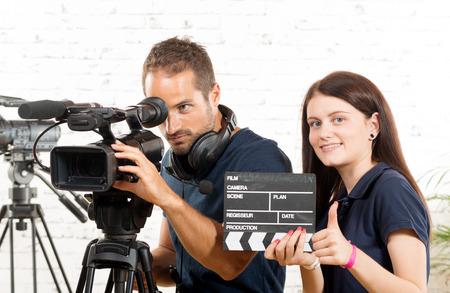 cine: un camarógrafo y una mujer joven con una cámara de cine