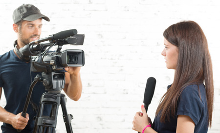 a young woman journalist with a microphone and a cameraman Foto de archivo