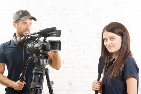 a young woman journalist with a microphone and a cameraman Stock Photo