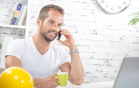 businessman smiling: a young business man drinking a cup of coffee, on phone