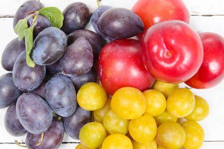 varieties: three varieties of plums on a white wooden table