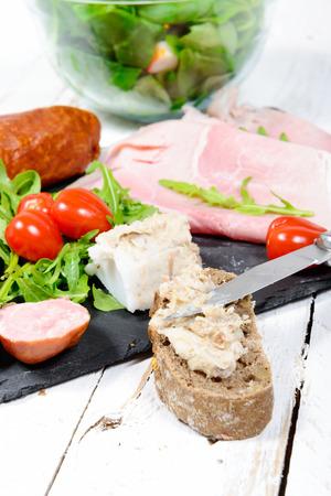 charcuter�a: plato de embutidos con pan y tomates en tabla de madera blanca