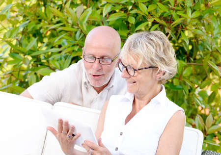 middle age couple: middle age couple, smiling, using a tablet in their garden