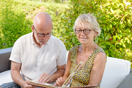 picture book: senior couple looking at a picture book, sitting in a sofa