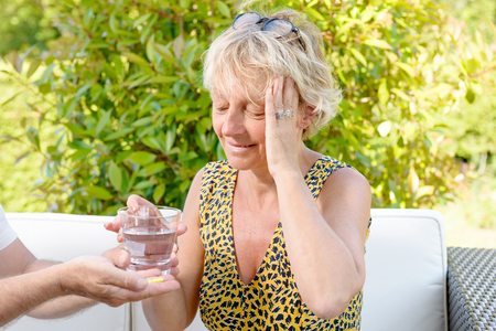 swallowing: a middle-aged woman with a headache, take a pill