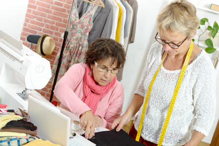 Two happy women sewing together in their fashion workshop