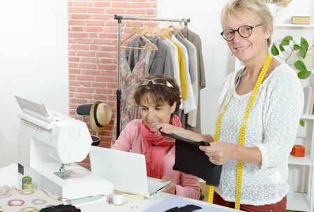 Two cheerful seamstresses working together in their fashion workshop