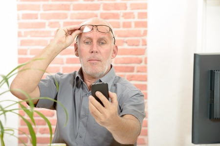 Mature man having trouble seeing cell phone screen because of vision problems Foto de archivo