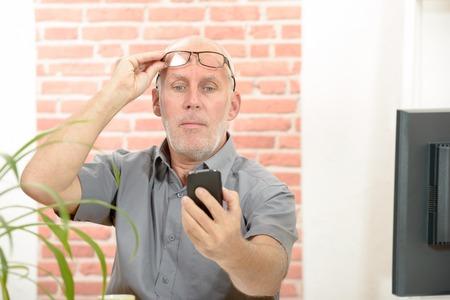 Oudere man problemen met het zien van mobiele telefoon scherm als gevolg van problemen met het gezichtsvermogen