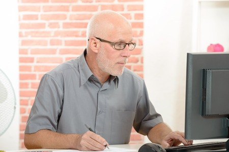 A Senior businessman with red eyeglasses working on computer