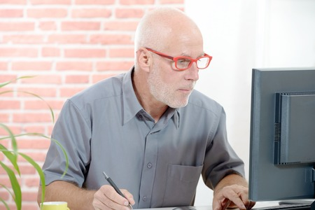businessman working at his computer: Senior businessman working on computer in his office