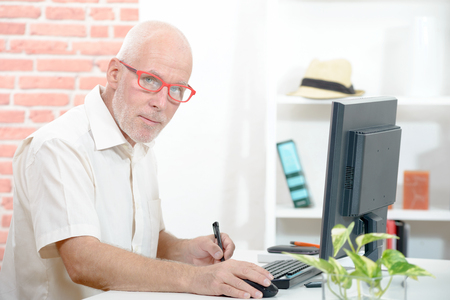 businessman working at his computer: Senior businessman working on computer in his office