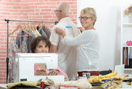 A seamstress takes action on the client with a tape measure