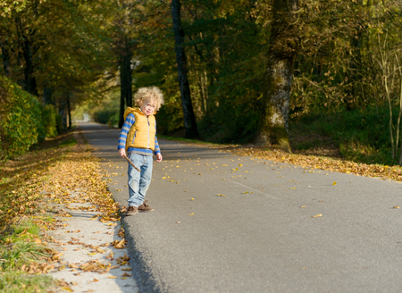 hoodlum: a little blond boy on the side of a small road, an autumn day