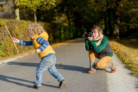 parental love: Cheerful mother taking picture of her cute little son in the park, happy young family having fun outdoors, parental love and enjoyment