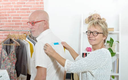 needlewoman: A seamstress takes action on the client with a tape measure