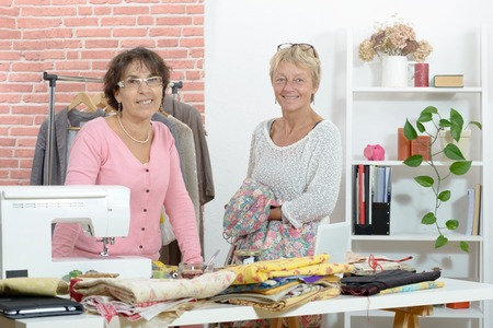 working place: Two cheerful seamstresses working together in their fashion workshop