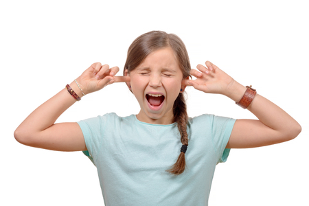 closes eyes: young girl stops his ears with his hands and closes her eyes on white background Stock Photo