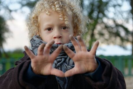 dirty blond: A little blond boy showing his hands dirty Stock Photo