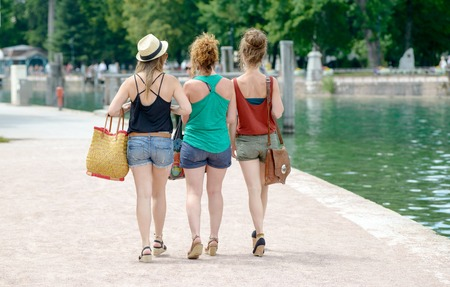 go to the shopping: Girlfriend go shopping. Three attractive young girl holding shopping bags . View from the back of girls