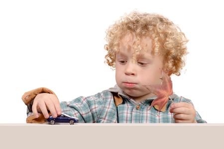 juguetes: un pequeño muchacho rubio jugando con un coche de juguete Foto de archivo
