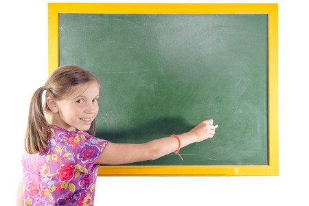schooler: First grade pupil a girl writing on green blackboard isolated on white background Stock Photo