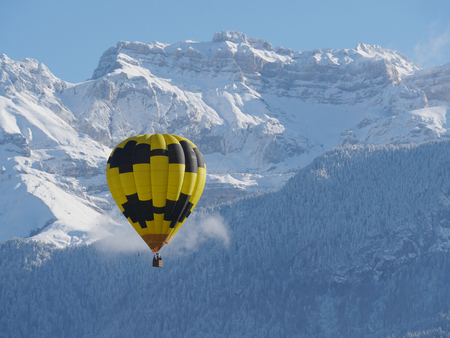 a black and yellow hot air balloon with the snowy mountain at the back