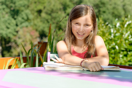 learns: a schoolgirl learns his lessons on the garden table, in summer