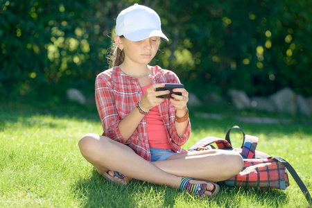 schoolgirl: a pretty schoolgirl sitting on the grass playing with his smartphone