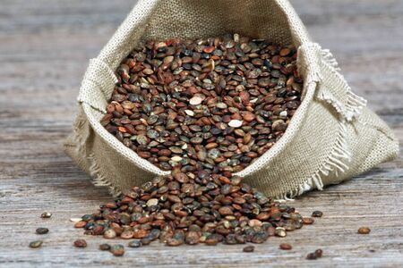 hessian bag: lentils in a small hessian bag on wooden table Stock Photo