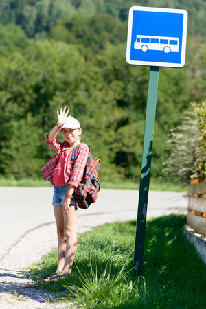 bookbag: a schoolgirl with a white cap, goes to school with bus
