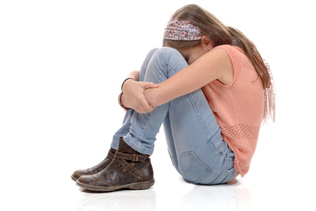 sulking: a little girl sitting on the floor and sulking, white background