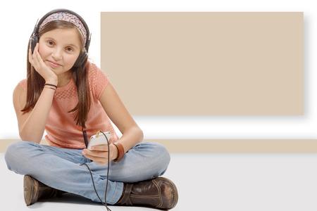 crosslegged: a young teenager sitting cross-legged on the floor, listen music Stock Photo