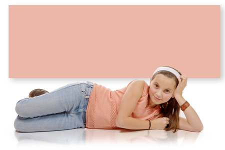 cute blonde: a portrait of smiling little girl lying on the floor isolated on white background
