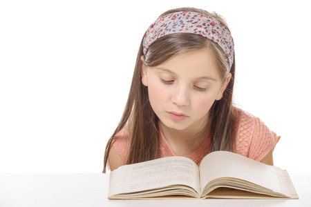 a little student girl studying and reading book at school