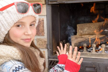 fire place: Winter at home, a pretty young girl sitting near the fire place