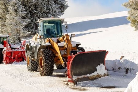 snow plow: a large tractor with snow plow  during a winter Stock Photo