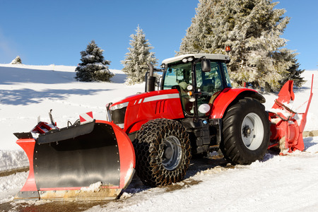 snow plow: a large red tractor with snow plow  during a winter Stock Photo