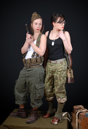 two sexy women: two sexy women posing in WW2 military uniform and weapons Stock Photo