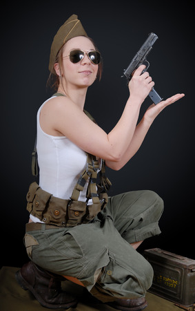 ww2: a sexy young woman posing in WW2 military uniform and a weapon